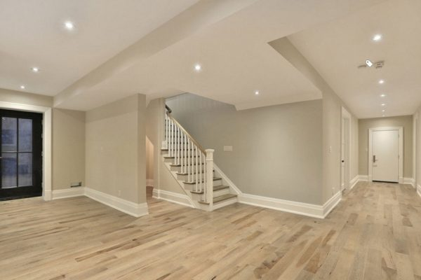 Renovated basement with grey walls and hardwood floor